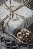 Il contenitore di regalo ha avvolto il panno di tela e decorato con cavo, la iuta, decorazione di natale sui bordi di legno d'ann Fotografia Stock Libera da Diritti