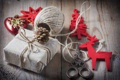 Il contenitore di regalo ha avvolto il panno di tela e decorato con cavo, la iuta, decorazione di natale sui bordi di legno d'ann Immagini Stock Libere da Diritti