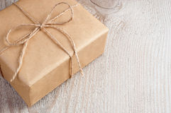 Il contenitore di regalo ha imballato in carta marrone ed in cordicella su vecchio Fotografie Stock