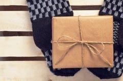 Il contenitore di regalo ha imballato la carta marrone e la cordicella sui guanti fatti a mano che si trovano sull'annata di legn Immagine Stock