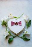 Il contenitore di regalo nella forma di cuore circondata con alstroemeria fiorisce Immagine Stock