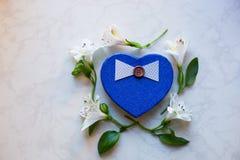 Il contenitore di regalo nella forma di cuore circondata con alstroemeria fiorisce Fotografia Stock Libera da Diritti