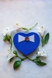 Il contenitore di regalo nella forma di cuore circondata con alstroemeria fiorisce Immagini Stock