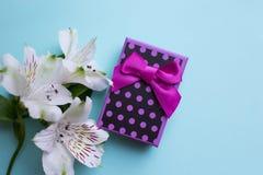 Il contenitore di regalo porpora con alstroemeria fiorisce sul backgrou blu-chiaro Fotografia Stock