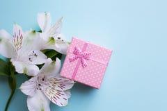Il contenitore di regalo rosa con alstroemeria fiorisce su fondo blu-chiaro Immagine Stock