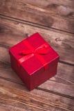 Il contenitore di regalo rosso avvolto su fondo di legno può usare il giorno di madre di giorno di S. Valentino o celebrare il gi Fotografie Stock Libere da Diritti