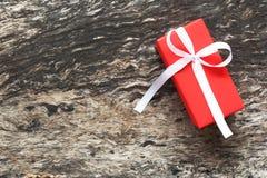 Il contenitore di regalo rosso con il nastro ed il nastro bianco si piegano su vecchio e su rustico Fotografia Stock