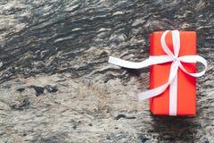 Il contenitore di regalo rosso con il nastro ed il nastro bianco si piegano su vecchio e su rustico Fotografie Stock Libere da Diritti
