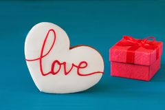 Il contenitore di regalo rosso del giorno di biglietti di S. Valentino della st con l'arco ed il pan di zenzero sotto forma di cu Fotografie Stock Libere da Diritti