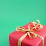 Il contenitore di regalo rosso di Natale con l'arco del nastro della carta marrone Fotografie Stock Libere da Diritti
