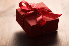 Il contenitore di regalo rosso ha legato il nastro rosso sulla tavola di legno Immagine Stock Libera da Diritti