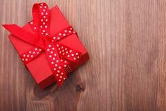 Il contenitore di regalo rosso ha legato il nastro rosso sulla tavola di legno Immagini Stock Libere da Diritti