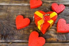 Il contenitore di regalo rosso nella forma che ha modellato la pantofola di legno del pendente con il diamante, lei sta su un fon Immagine Stock