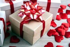Il contenitore di regalo su un fondo e su un cuore grigi del tessuto modella Immagine Stock Libera da Diritti