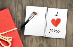 Il contenitore ed il messaggio di regalo ti amo in scritto in in taccuino e nella forma rossa del cuore hanno dipinto con il penn immagini stock