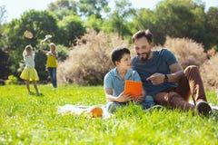 Il contenuto parents intrattenere i loro bambini immagine stock