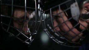 Il contrappeso fra i giocatori di hockey Primo piano di un portiere ed in avanti un faccia a faccia, fronte alla fronte video d archivio