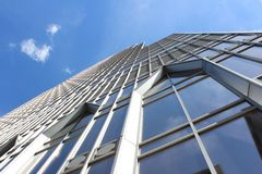 Il contrasto di costruzione con il cielo luminoso, blu, chiaro ha riflesso nelle sue finestre a Montreal del centro, Canada immagini stock