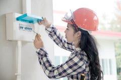 Il controllo femminile asiatico dell'ingegnere o dell'elettricista o ispeziona l'interruttore del sistema elettrico immagine stock libera da diritti