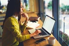 Il copywriter sicuro si è concentrato sul lavoro a distanza che si siede in caffè interno moderno con il wifi Fotografie Stock Libere da Diritti