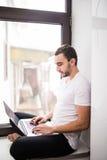 Il coraggioso, bello, uno studente che lavora ad un davanzale con un computer portatile lavoratore che comunica su Internet Fotografia Stock Libera da Diritti