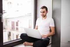 Il coraggioso, bello, uno studente che lavora ad un davanzale con un computer portatile lavoratore che comunica su Internet Immagine Stock Libera da Diritti
