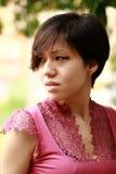 Il Coreano emozionale ha spaventato sembrare sinistro, vestito da rosa, primo piano Fotografia Stock