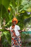 Il corpo completo verticale di una donna afroamericana allegra pose nazionali variopinte luminose d'uso di un vestito fotografia stock libera da diritti