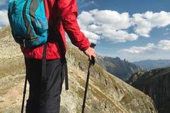Il corpo dell'uomo con uno zaino ed i pali di trekking sta sopra una roccia contro la valle rocciosa del fondo alta dentro immagini stock libere da diritti