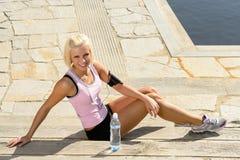 Il corpo della donna di sport si distende la terra di pietra di seduta Immagini Stock