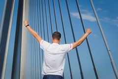 Il corridore atletico dell'uomo ha alzato le sue armi su che stanno sul ponte Immagini Stock
