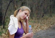 Il corridore della donna sta pareggiando sul sentiero nel bosco in parco Immagini Stock