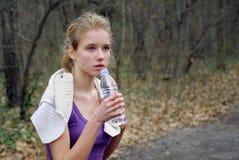 Il corridore della donna sta pareggiando sul sentiero nel bosco in parco Immagini Stock Libere da Diritti