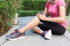 Il corridore della donna tocca il suo ginocchio danneggiato Fotografie Stock Libere da Diritti