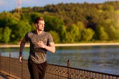 Il corridore di forma fisica e di sport equipaggia il funzionamento nel parco immagine stock