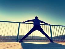 Il corridore di mattina in ghette nere alte fa il corpo che allunga sul percorso del ponte Esercitazione all'aperto Fotografia Stock Libera da Diritti