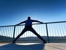 Il corridore di mattina in ghette nere alte fa il corpo che allunga sul percorso del ponte Esercitazione all'aperto Immagini Stock Libere da Diritti