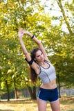 Il corridore femminile allunga le sue armi durante il riscaldamento Fotografie Stock