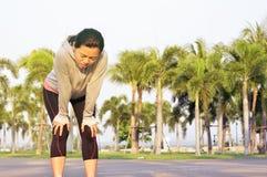 Il corridore femminile stanco ha preso una rottura dopo l'allenamento duro all'aperto Immagine Stock Libera da Diritti
