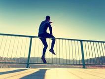 Il corridore in ghette nere fa il corpo che allunga sul percorso del ponte Corpo dell'uomo dei profili di Sun Immagini Stock