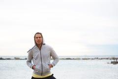 Il corridore maschio attraente si è vestito in maglietta felpata che sta sul fondo di orizzonte di mare fotografie stock