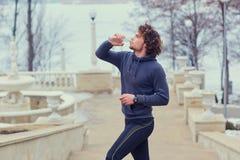 Il corridore maschio riccio beve l'acqua da un parco di imbottigliare sullo stai Fotografia Stock