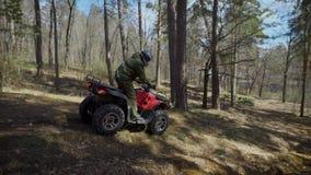 Il corridore nella foresta l'uomo guida lentamente il ATV sull'impalcatura di autunno Nella foresta ` s più facile prepararsi sul stock footage