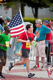 Il corridore porta la bandiera americana nella corsa di strada di Atlanta del 4 luglio Fotografie Stock Libere da Diritti