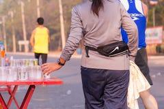 Il corridore prende un'acqua in una corsa maratona Immagine Stock