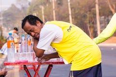 Il corridore prende un'acqua in una corsa maratona Immagini Stock