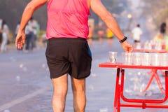 Il corridore prende un'acqua in una corsa maratona Immagini Stock Libere da Diritti