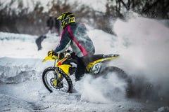 Il corridore su un motociclo guida a sua volta delle ruote uno spruzzo di neve e di fango Fotografia Stock