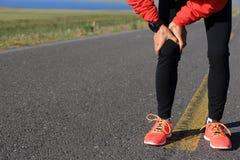 Il corridore tiene la sua gamba danneggiata sulla strada Fotografie Stock Libere da Diritti