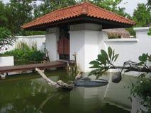 Il cortile con lo stagno, la parete bianca ed il portone immagine stock